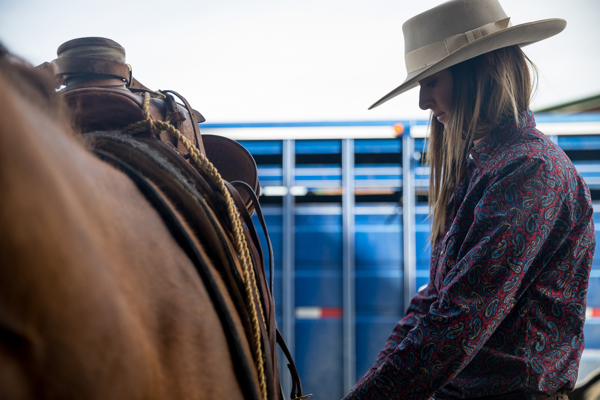Tightening the cinch before trailering the horses to a branding.