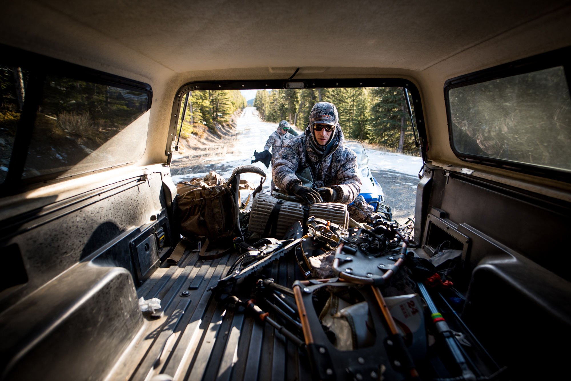 Adam Foss unloads his hunting gear from the bed of a truck.