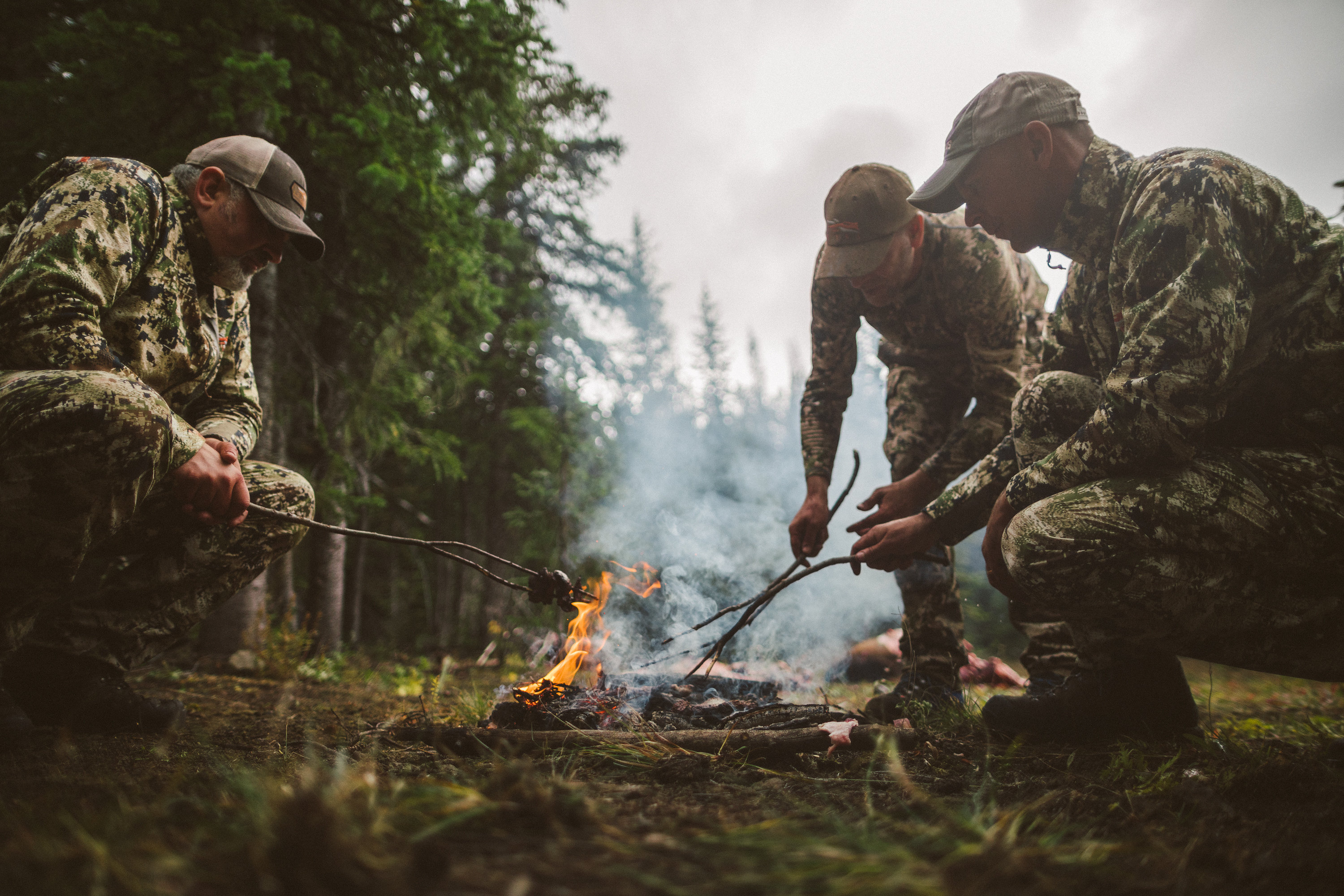 Hunters cook their harvest over an open fire.