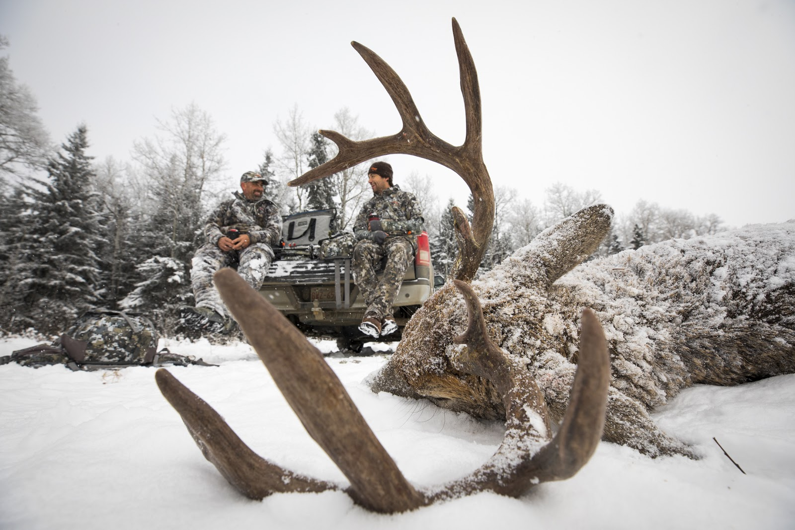 Whitetail hunters share stories with a buck on the ground.