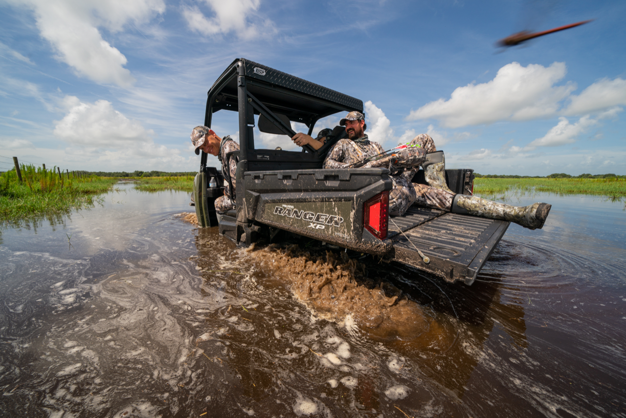 Whitetail hunters forge their way through water via a Polaris Ranger.