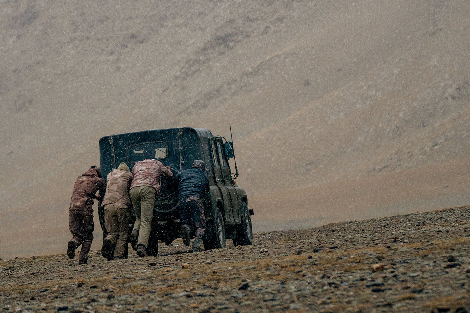 Pushing a jeep which broke down while attempting to reach the hunting destination.