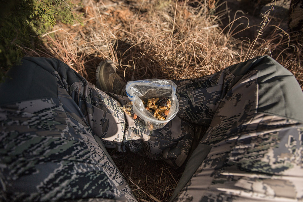 A hunter enjoys a snack bag of trail mix for backcountry nutrition.