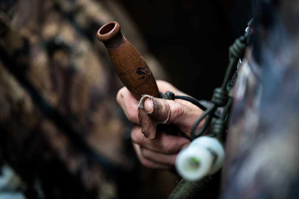 John Stephens watches ducks fly with one of his own ducks calls in hand