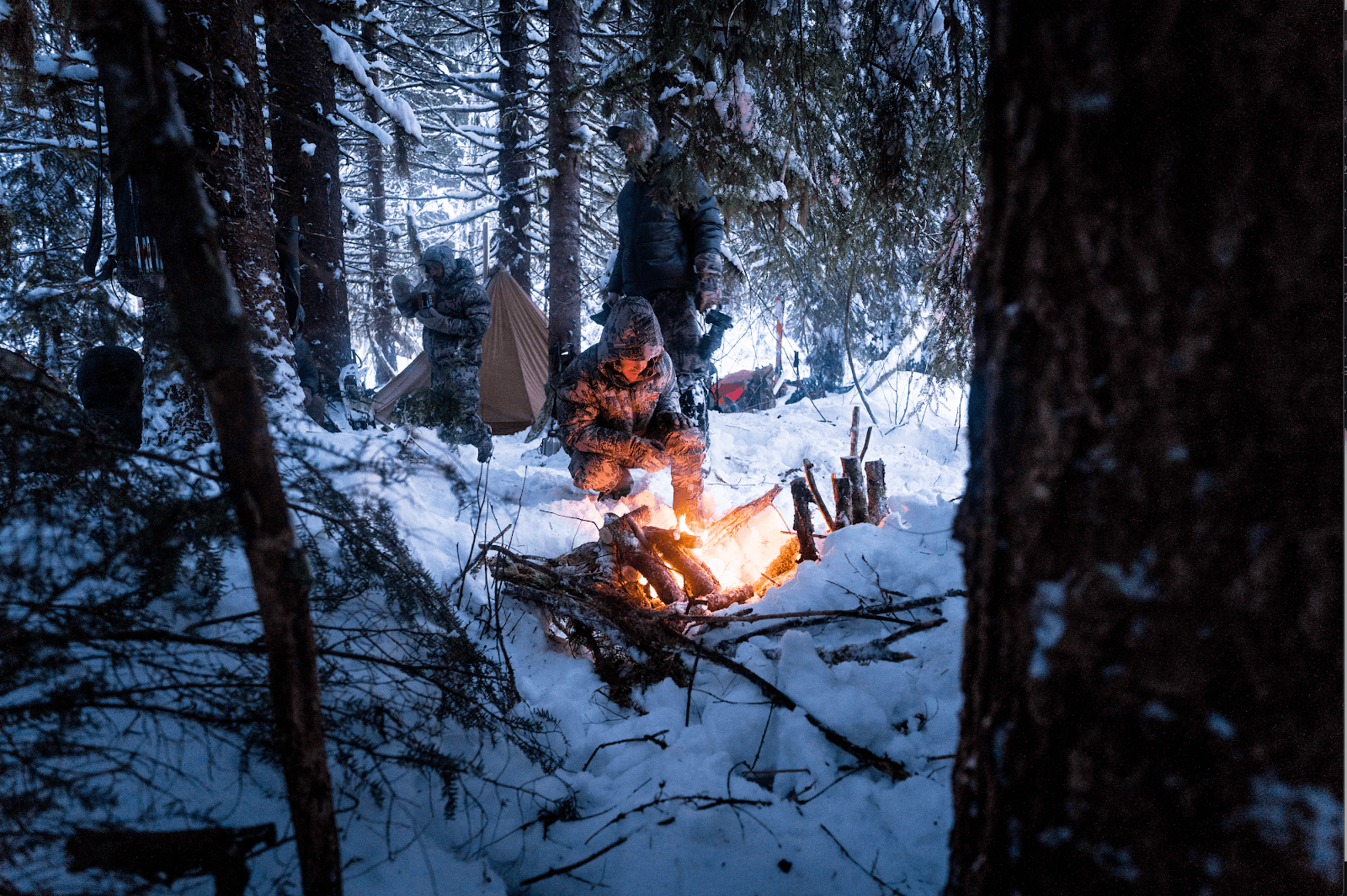 Hunters warm up next to a fire in the snow.