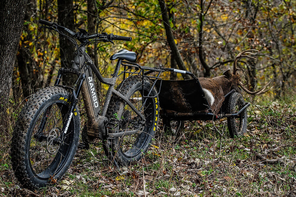 Whitetail buck getting ready to be hauled out of the woods via e-bike