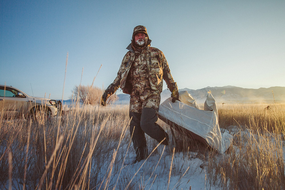 A goose hunter drags his layout blind behind him on a cold day.