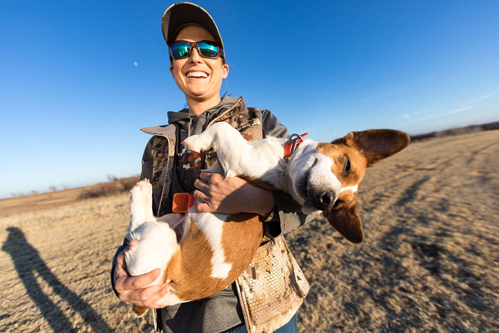 Dog trainer Alex Brittingham holds her Jack Russell Terrier, Gator.