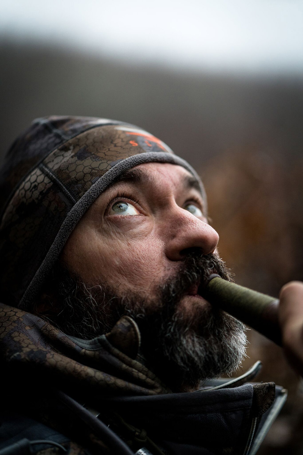 John Stephens has eyes to the sky as he blows a duck call.