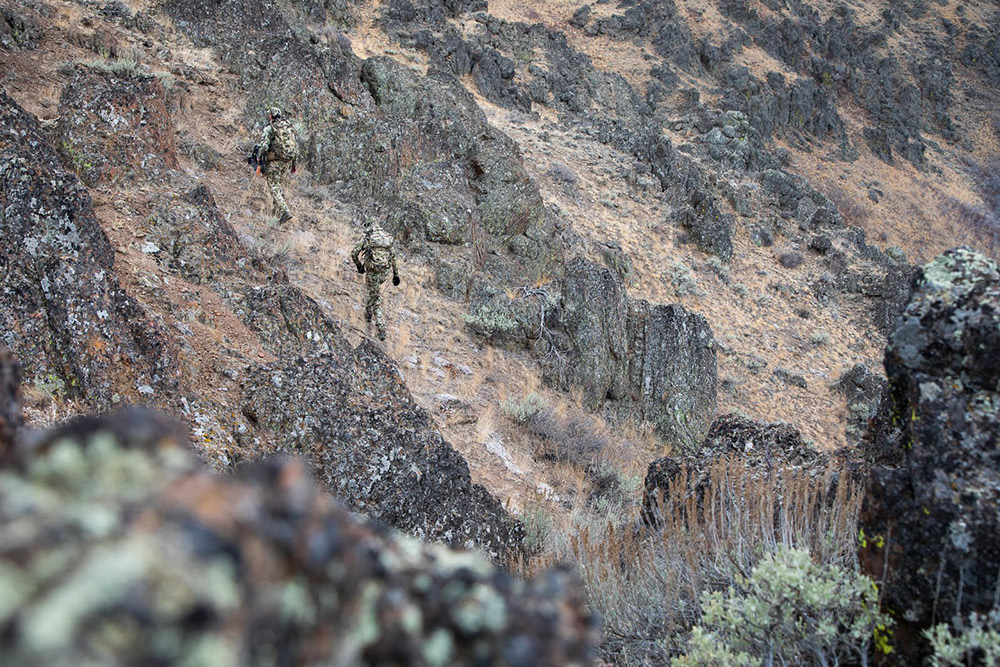 Hunters in Optifade Subalpine scale some rocky terrain.