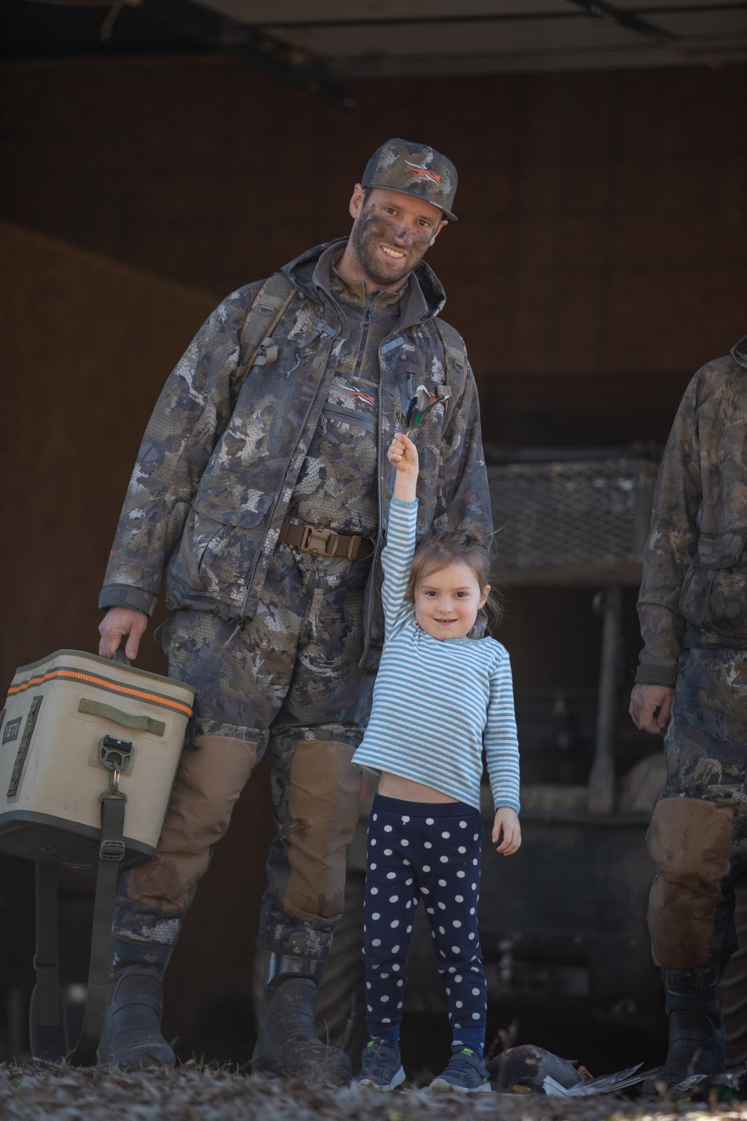 Father and daughter post-duck hunt. Yeti cooler in tote.