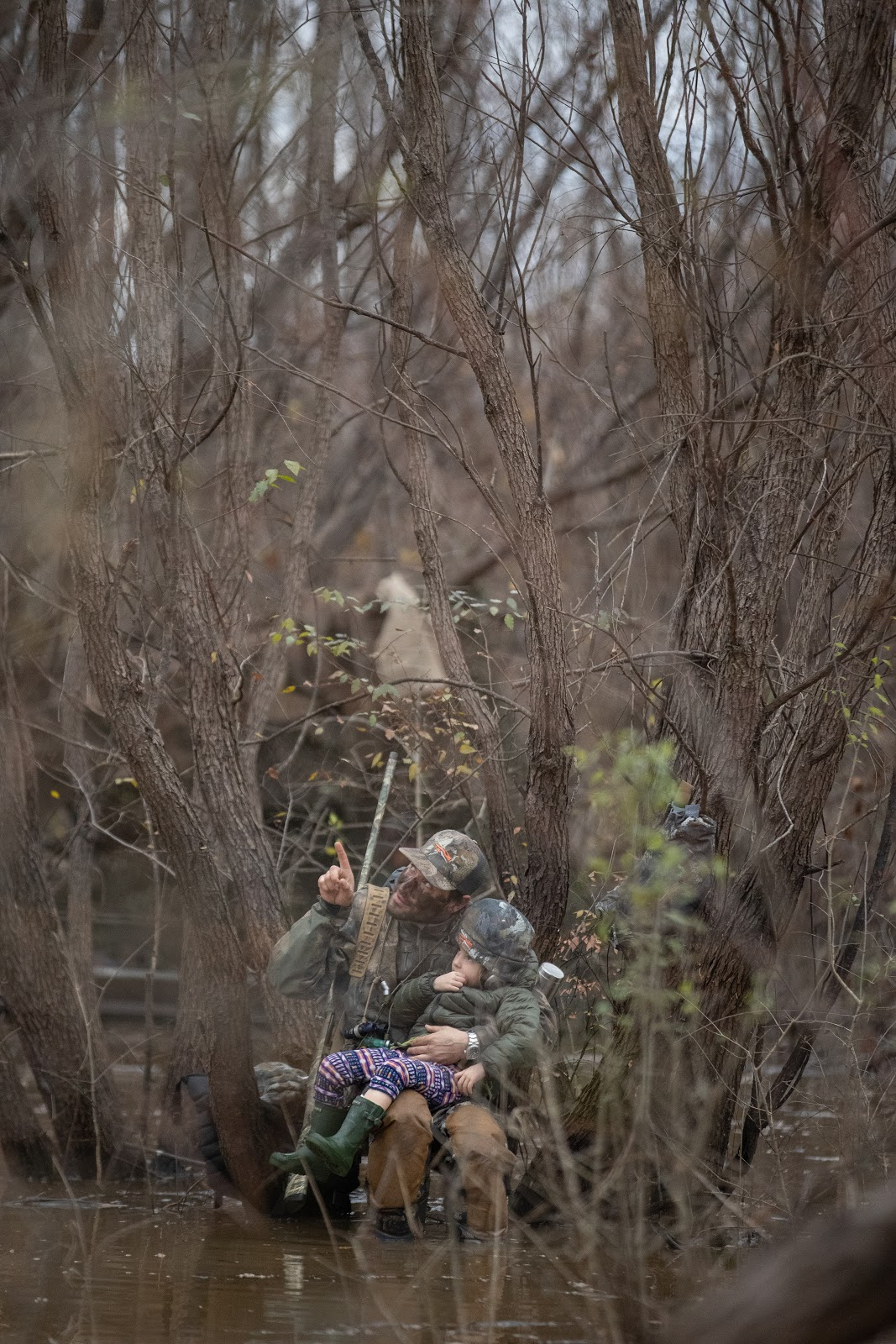 Father and daughter duck hunting in the timber.